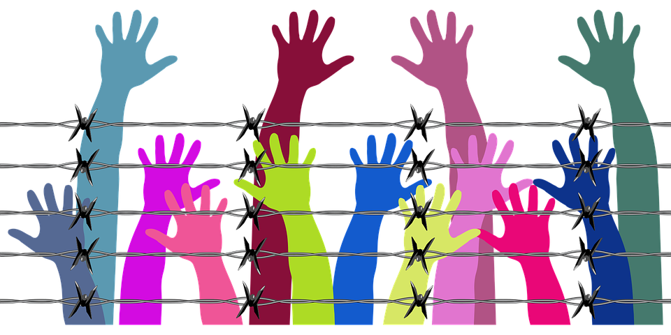 Pastel colored arms behind a barbed wire fencing
