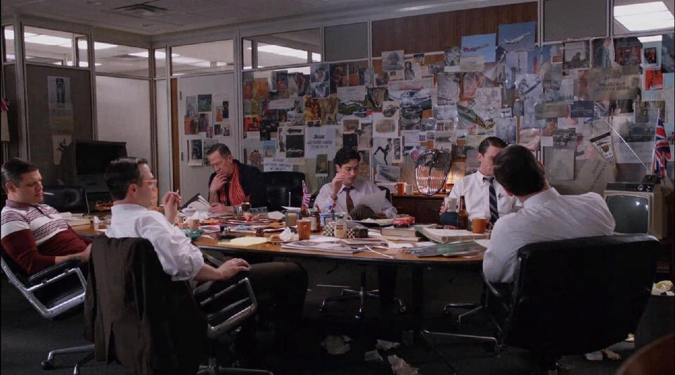 The mad men creative team comprised of 5 men, sitting around a boardroom table with a collage of inspiration on the wall