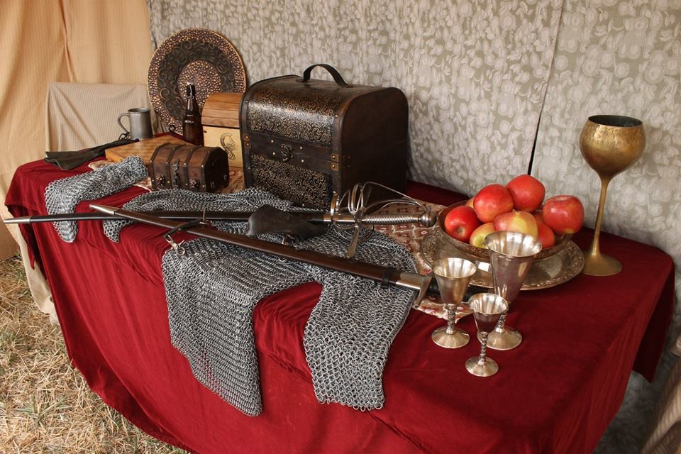 Chest, armor, weapons, plates and goblets and a bowl of fruit sit on a covered table.