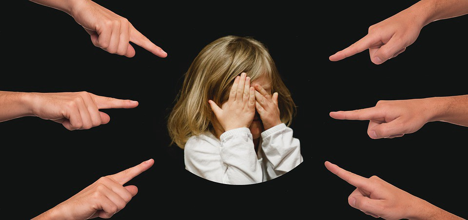 Picture of six fingers pointing to a child with hands covering her face as to protect herself from the pointing fingers.