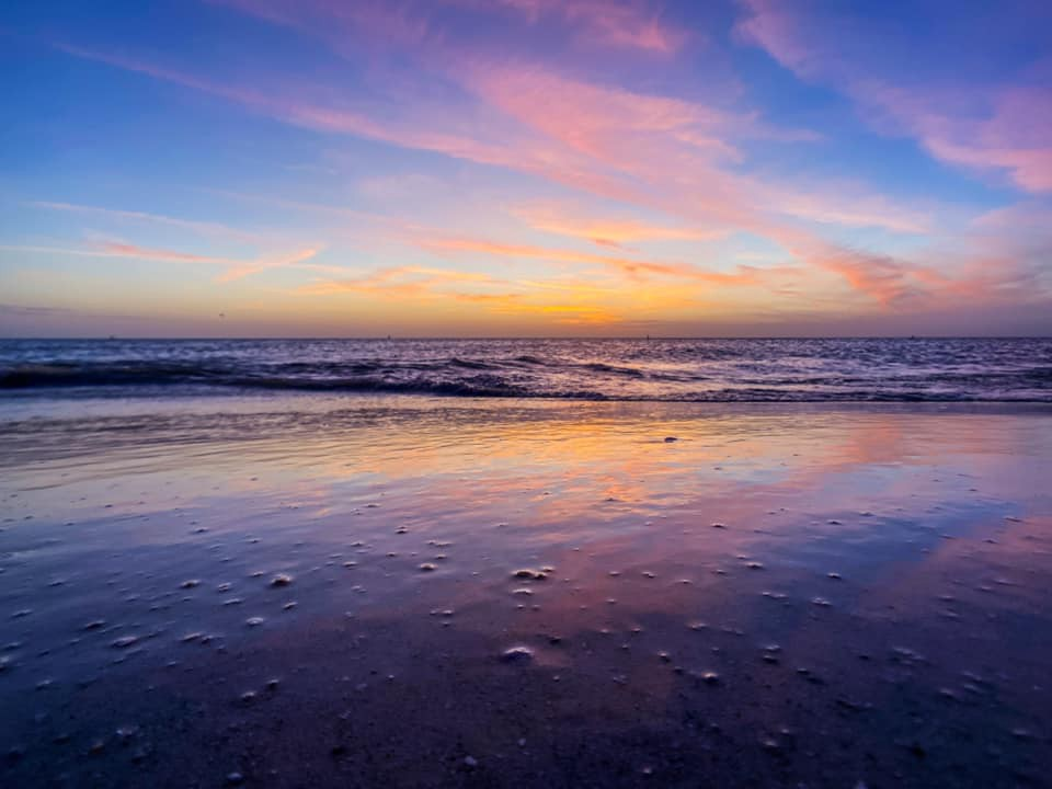 A pink and purple sunset over the Gulf of Mexico is reflected on the wet sand of a beach.