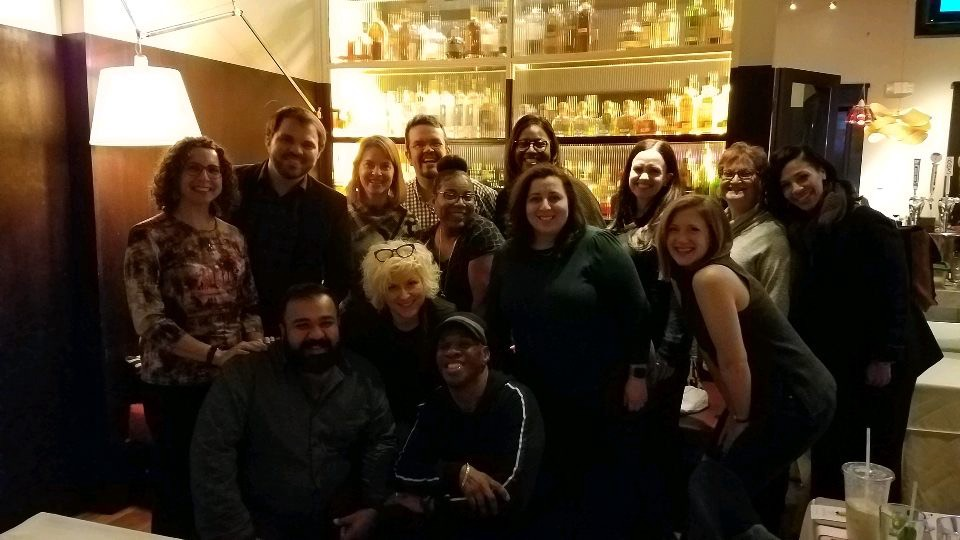The Arts Education council is standing in a group photo at a restaurant during their 2020 retreat
