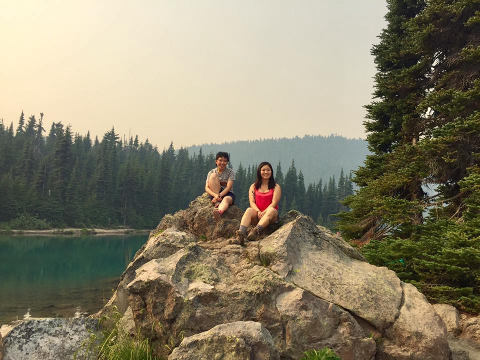 Two young women on a big rock in front of an emerald lake, forest, and mountains.