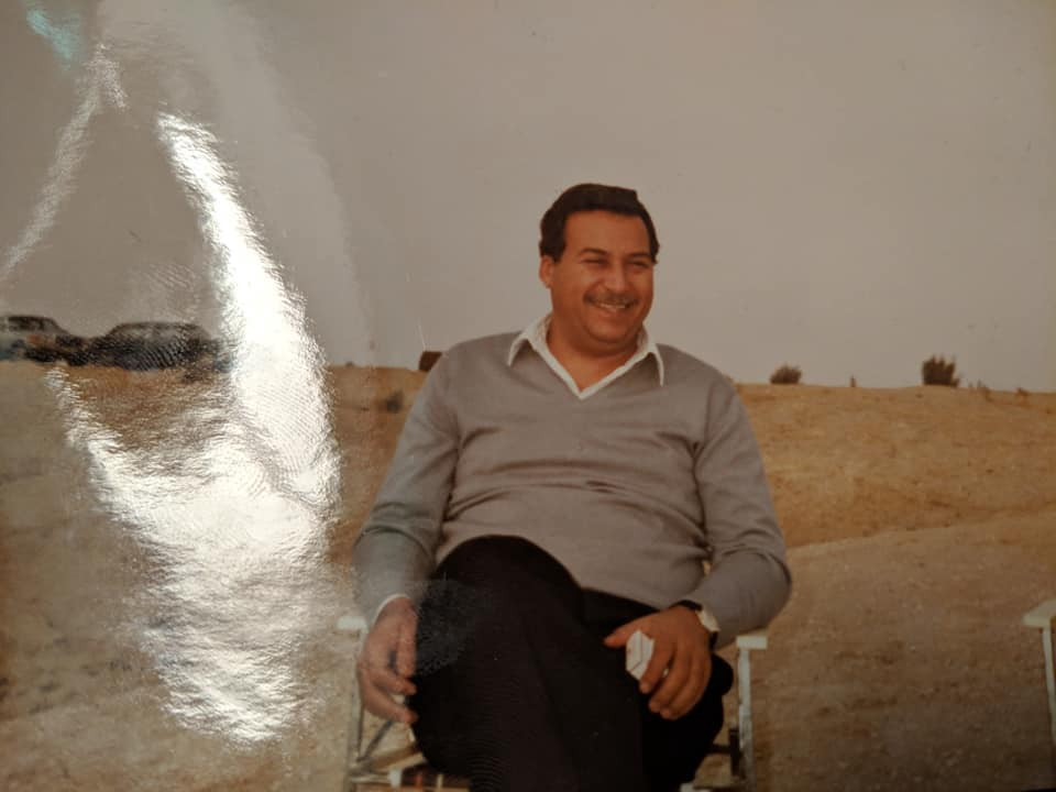 My father sits in a picnic chair with the Kuwaiti desert behind him. He is holding a pack of cigarettes.