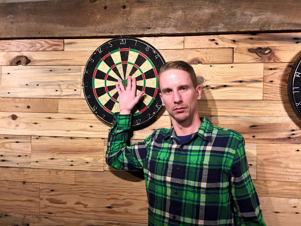 Matthew Bardeleben in green and blue plaid button up shirt with hand on dart board posing like Always Sunny in Philadelphia