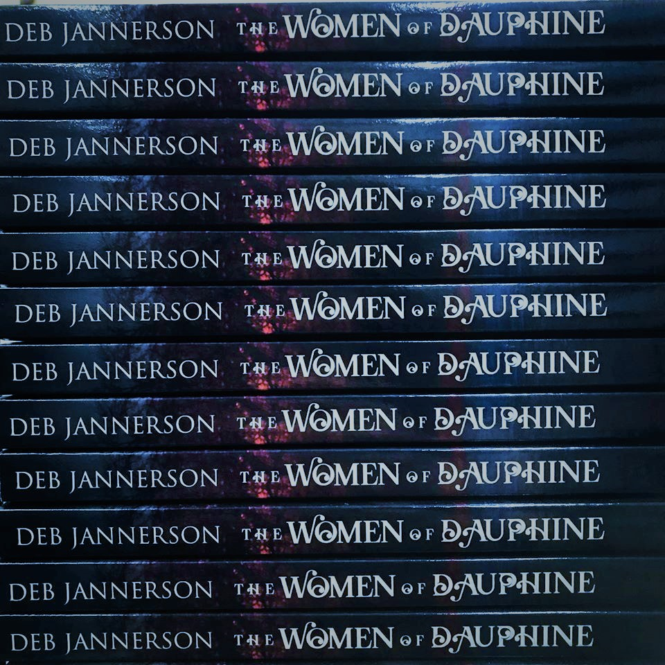 Blue-and-red spines of the book THE WOMEN OF DAUPHINE by the author, then named Deb Jannerson