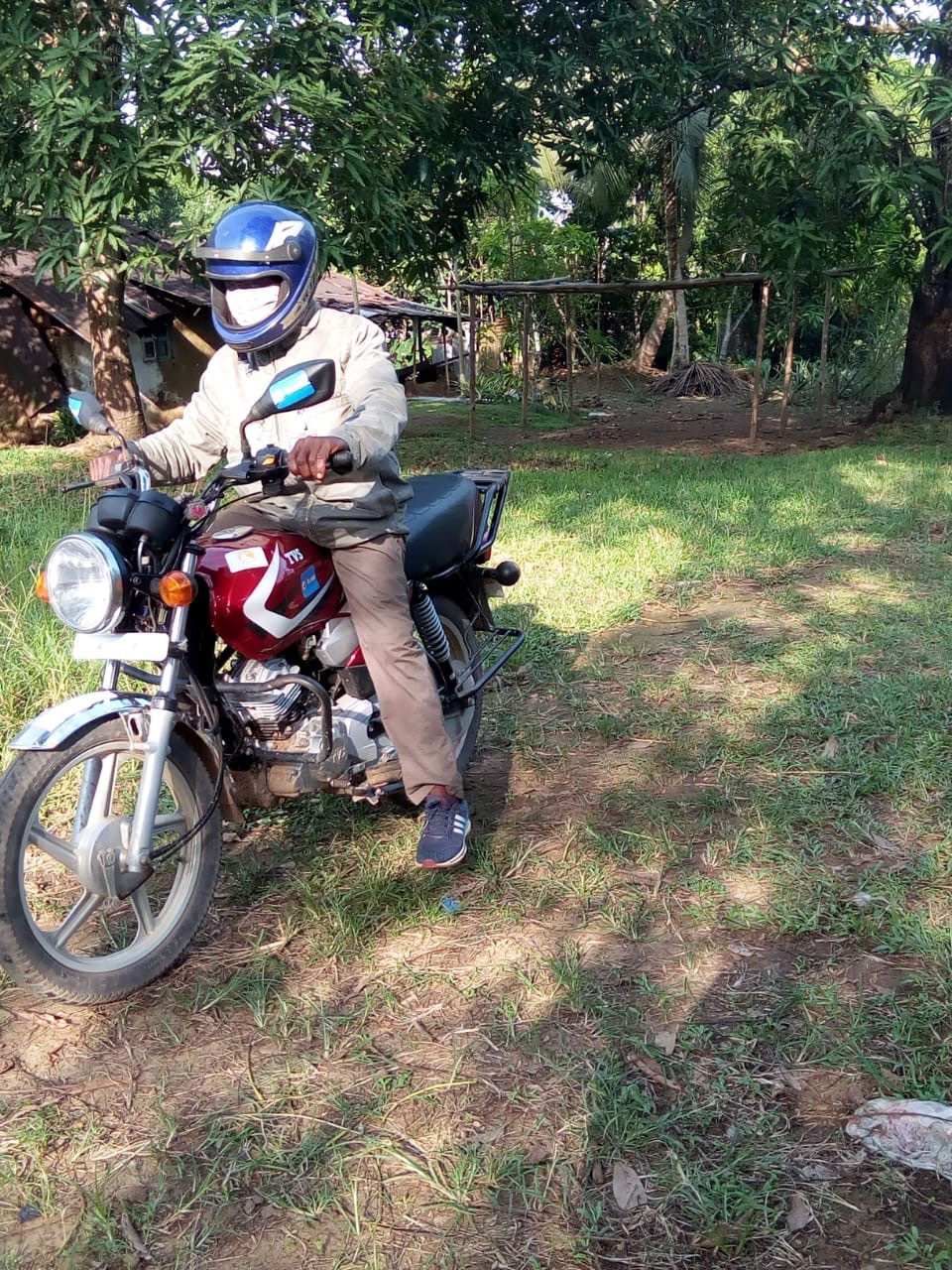 LIB Solar payment collector on his motorbike in rural Liberia