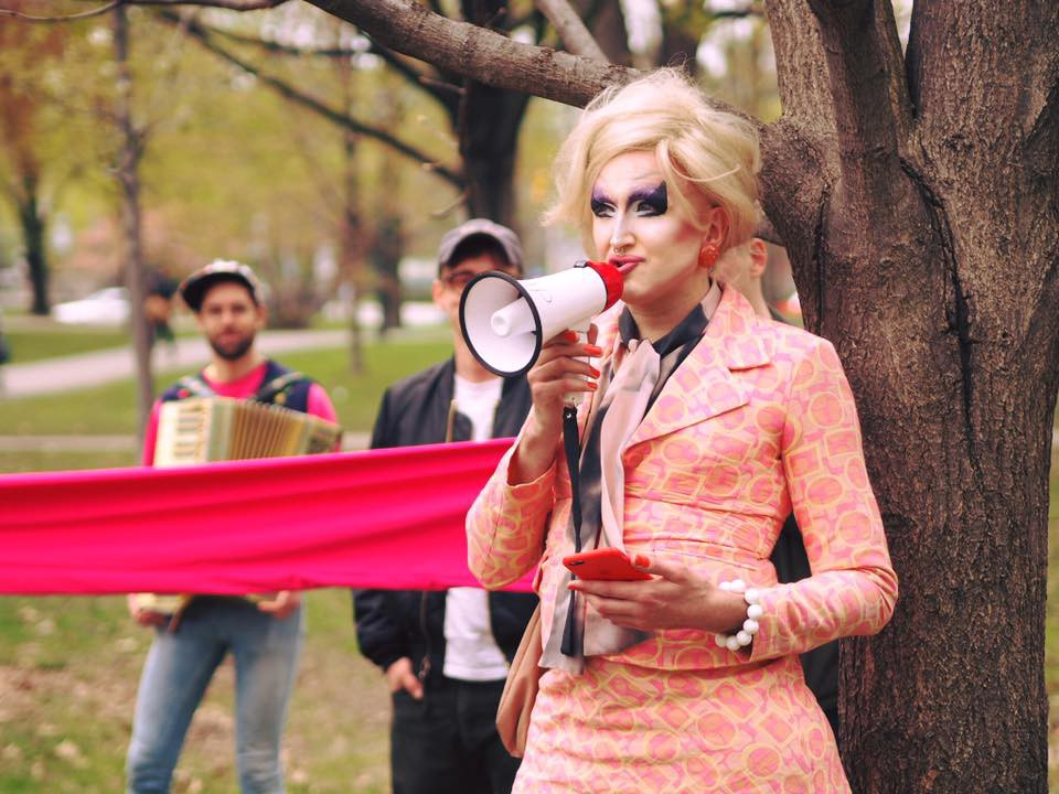 In a park, a drag queen speaks into a megaphone. Behind her two people stand near a giant pink ribbon
