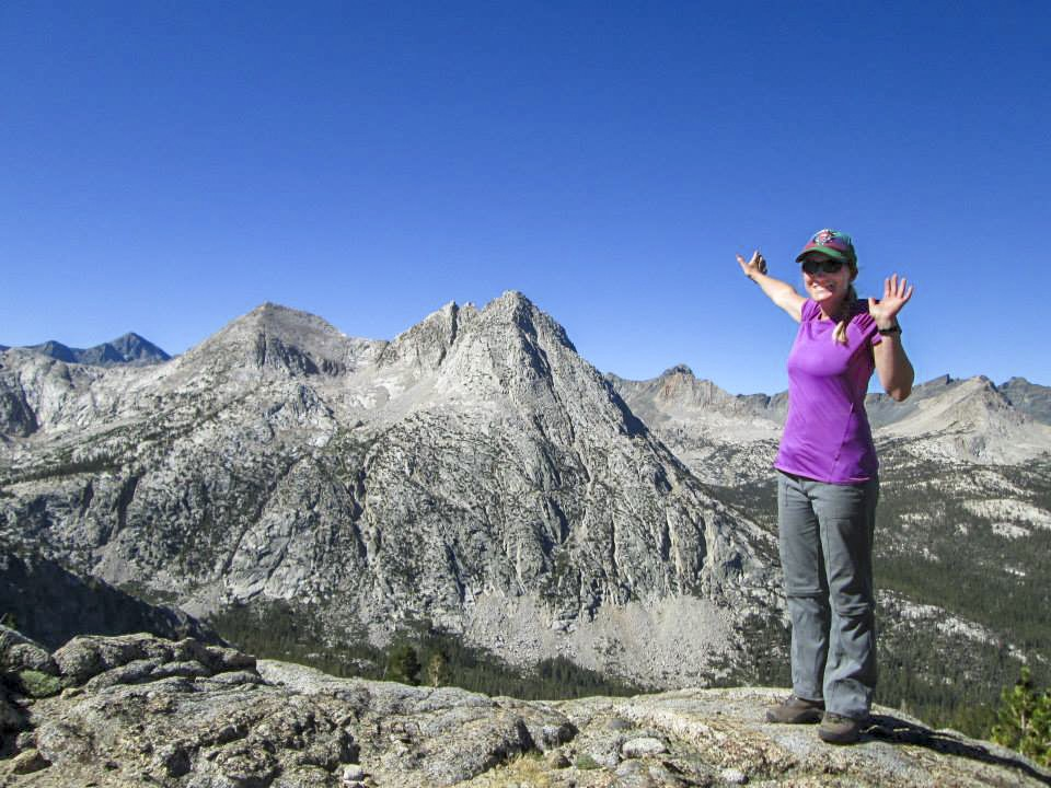 Stephanie stands on top of a mountain with a mountain range behind her