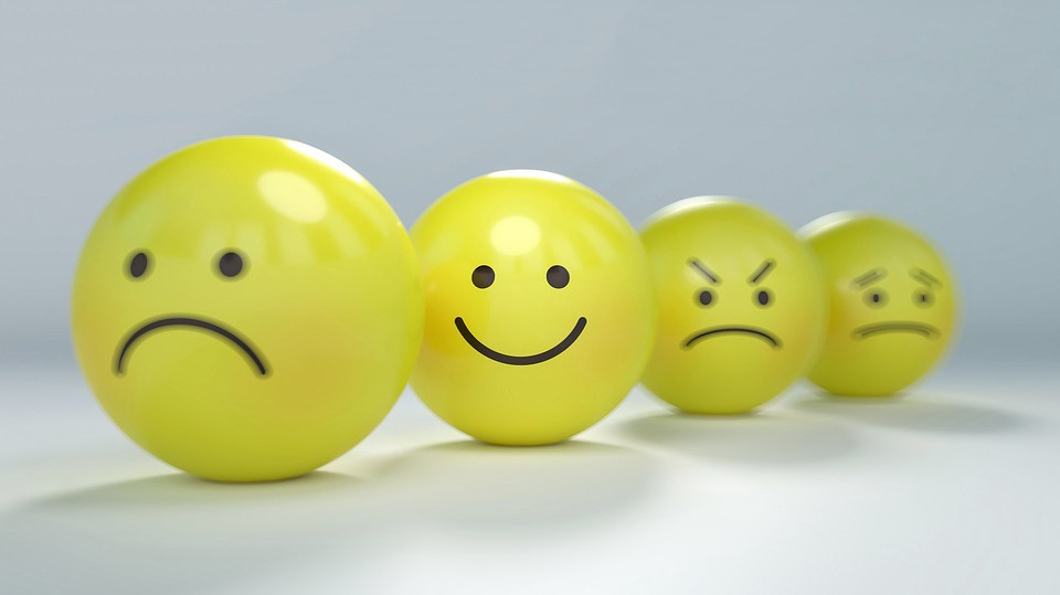 Multiple smiley faces, the happy one is focused, sad and angry ones are blurry.
