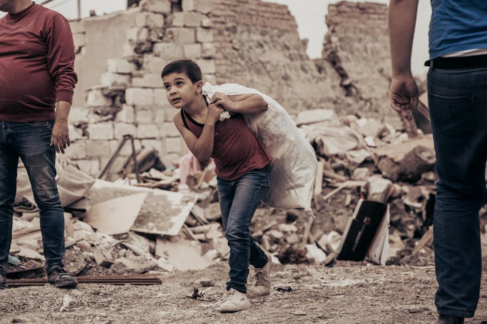 A young boy walks past buildings destroyed in a rocket attack on Ganja, Azerbaijan's second city. Image: Orkhan Rahmanli