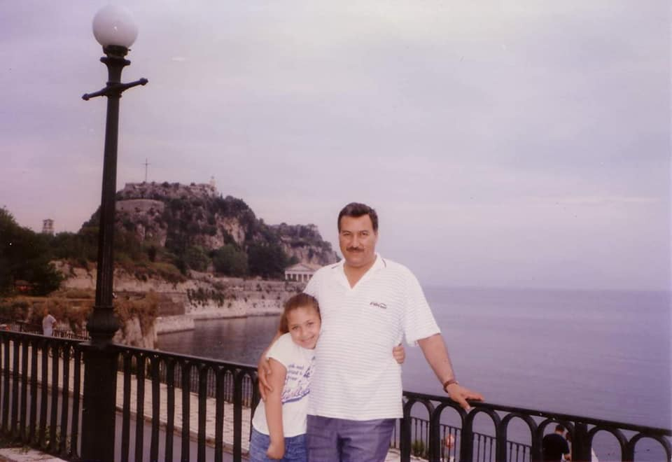 Me as a young child posing with my father in Greece. The ocean and a hillside are behind us.