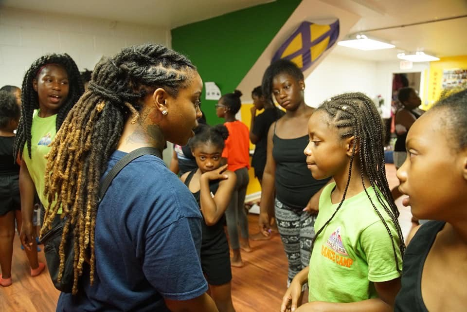 Woman with long hair twists wearing a t-shirt speaks with a group of students