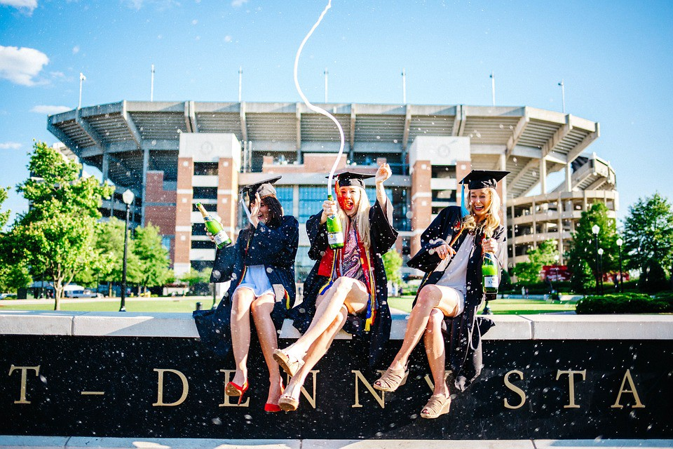 Three young women popping champagne to celebrate their recent graduation