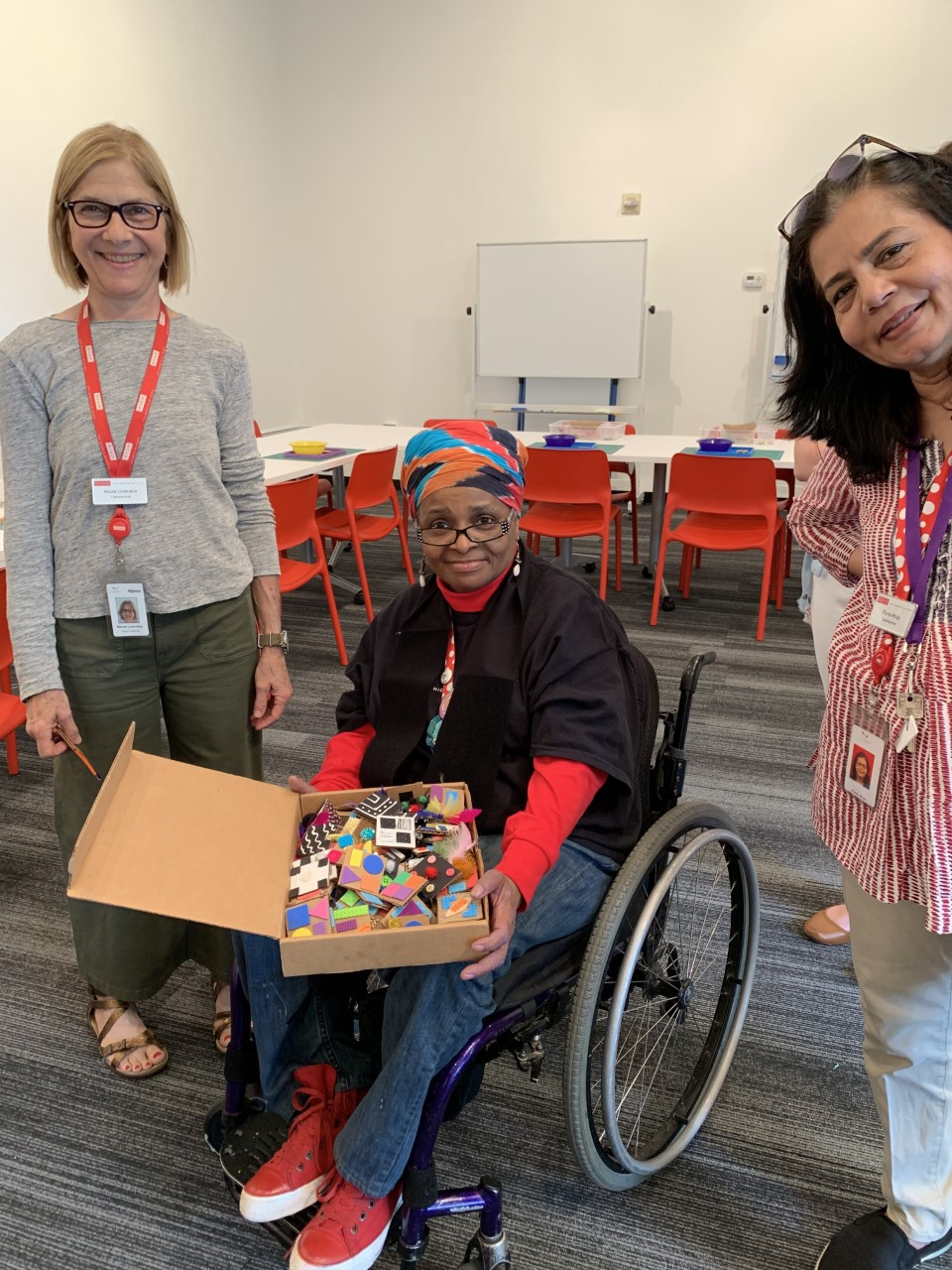 Two women stand on either side of a woman using a wheelchair holding a box of tactile materials.