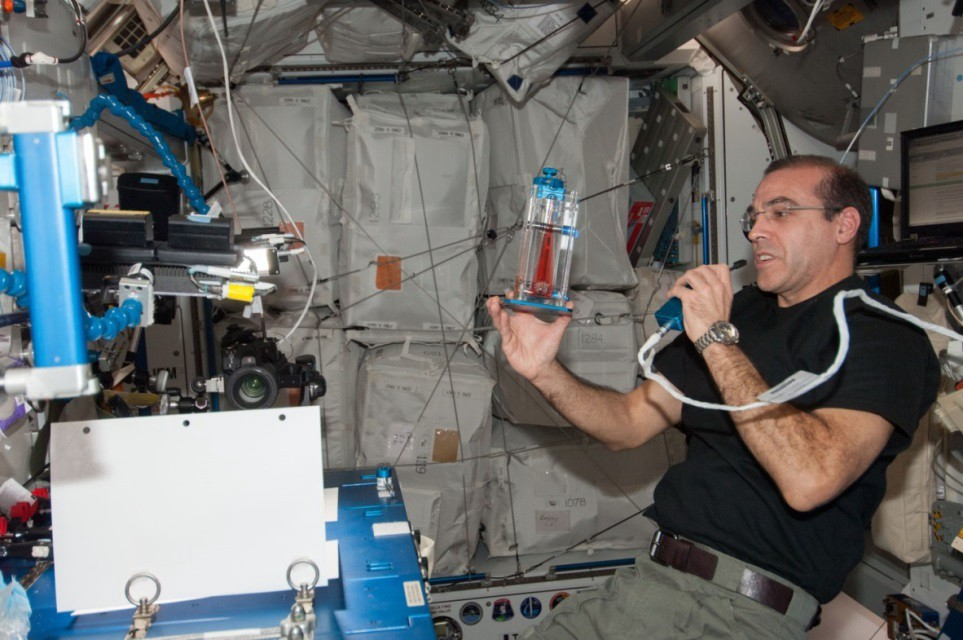 An astronaut blows into a tube, as a tube floats in front of him.