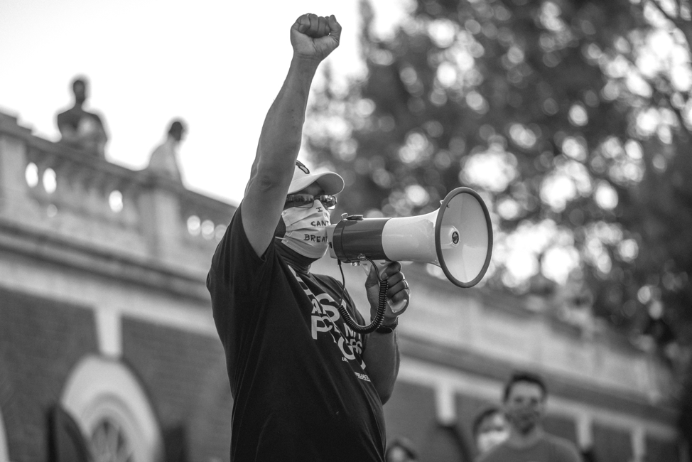 Don Gathers in front of the UVA Rotunda with fist raised.