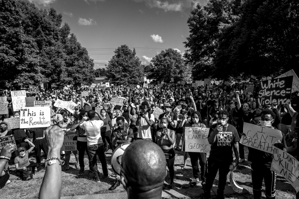Gathers giving a speech at a Charlottesville protest with hundreds of people.