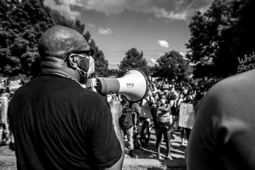 Gathers pictured from the back, holding a megaphone, and giving a speech to a large crowd.
