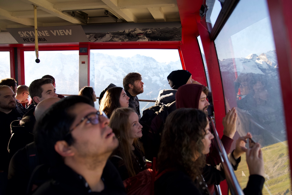 people standing in a gondola staring up at mountains
