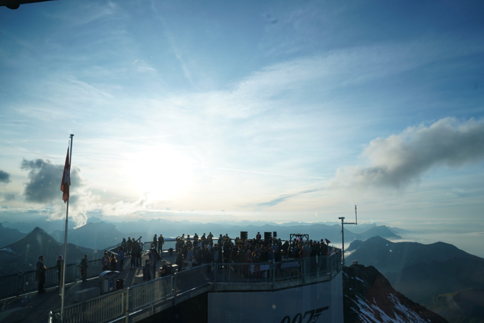 crowd of people standing on deck in front of mountains