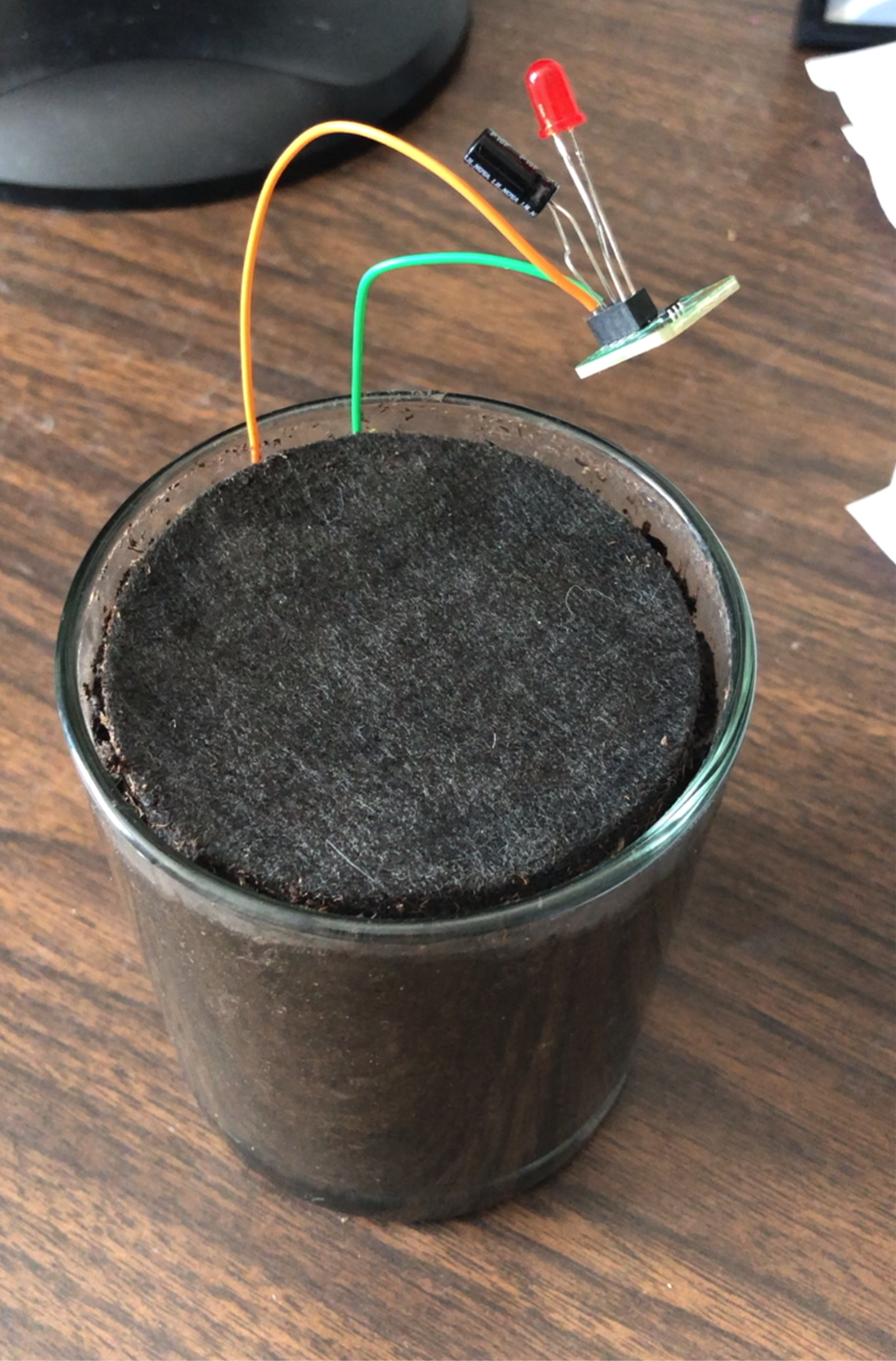 An image of soil in a small glass vase with wires and a blinker LED board coming out of it.