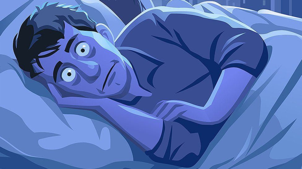 Man lying awake with his eyes wide open due to insomnia