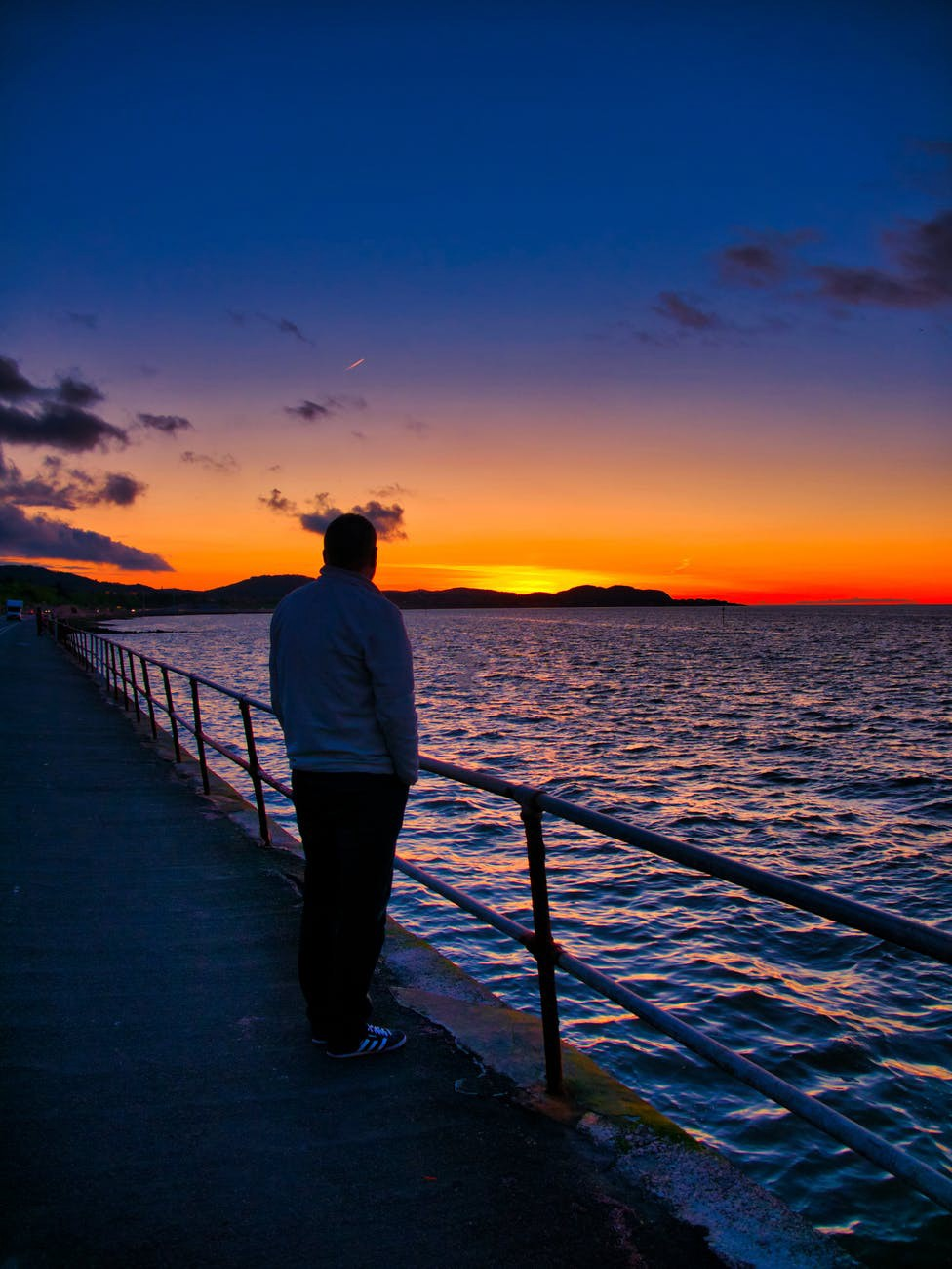 A man is watching the sunset over the sea all by himself.