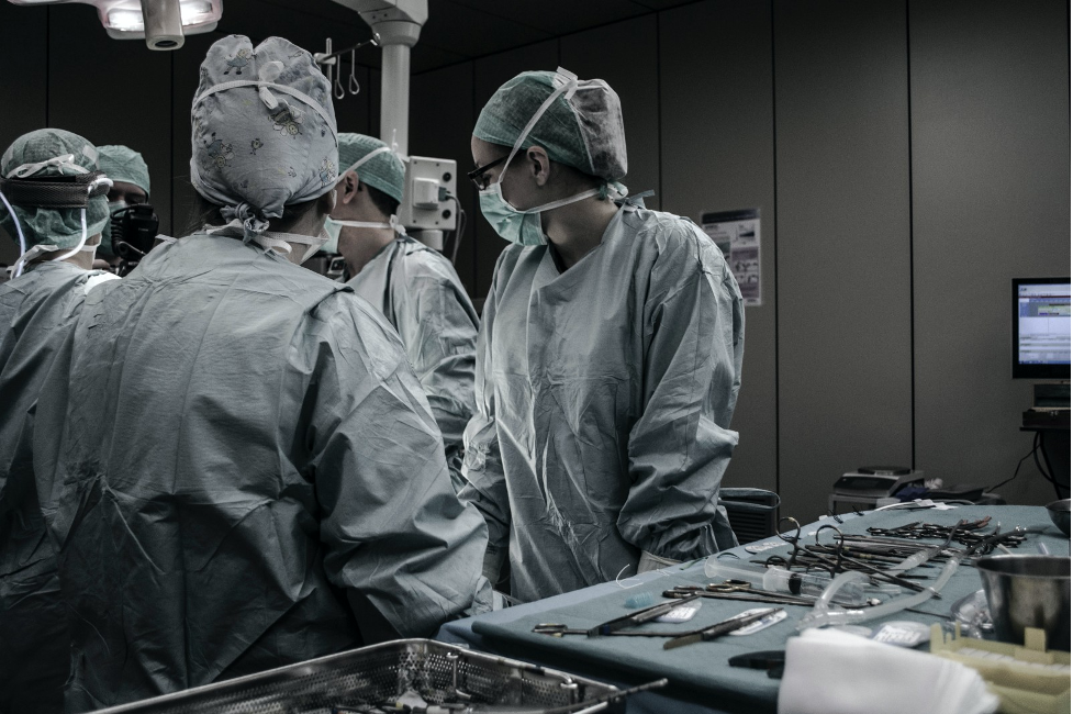 Individuals in face masks, scrub caps, and gowns standing in an operating room next to a table of tools.