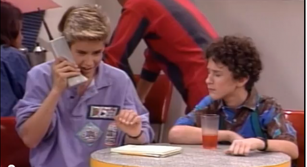 Still of Saved By the Bell from the 1990s, Screech and Zack sitting at The Max while Zack's on his hulking cell phone