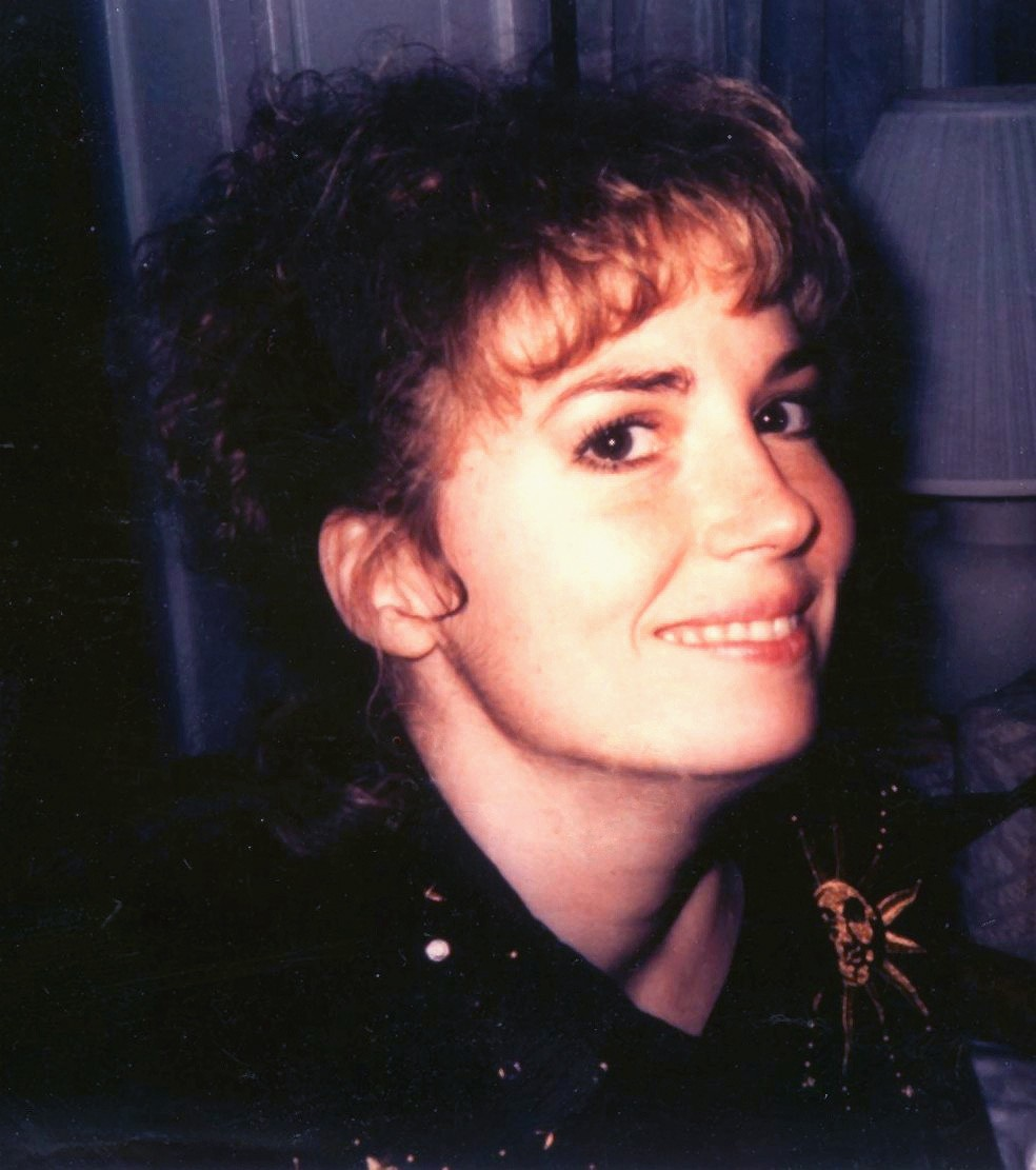 Portrait of Lisa McPherson. McPherson is smiling and looking over her rigths shoulder, directly into the camera.