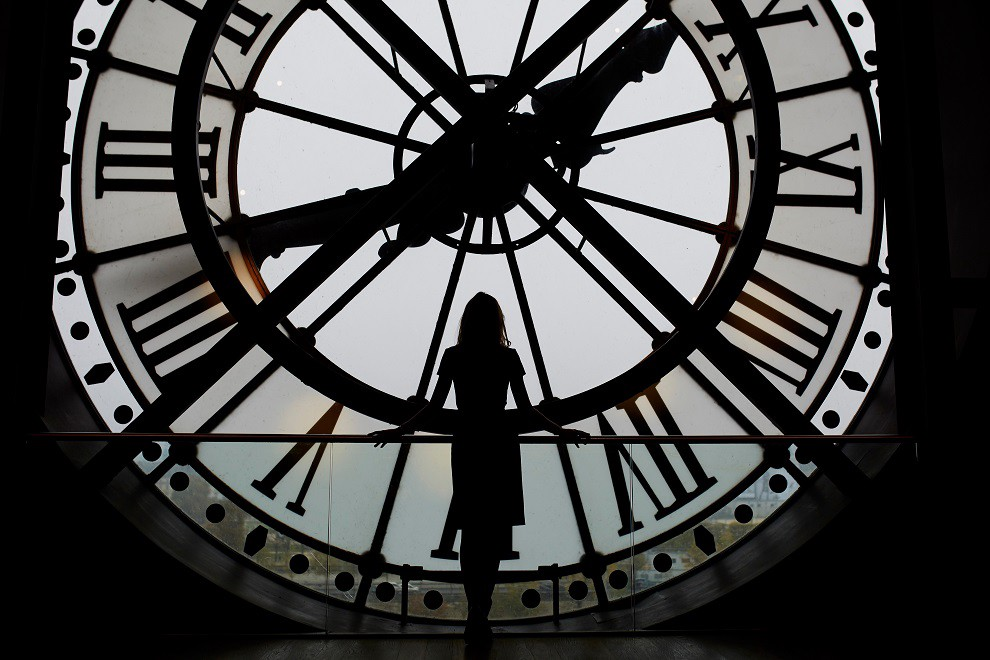 The silhouette of a tall woman stands at a large portrait window facing a clock