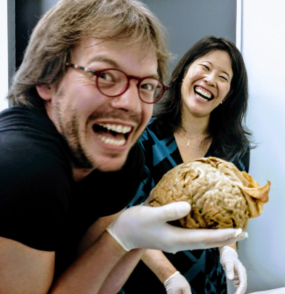 The author holds a brain in the foreground while laughing fiendishly, as Dr. Suzuki laughs from behind.