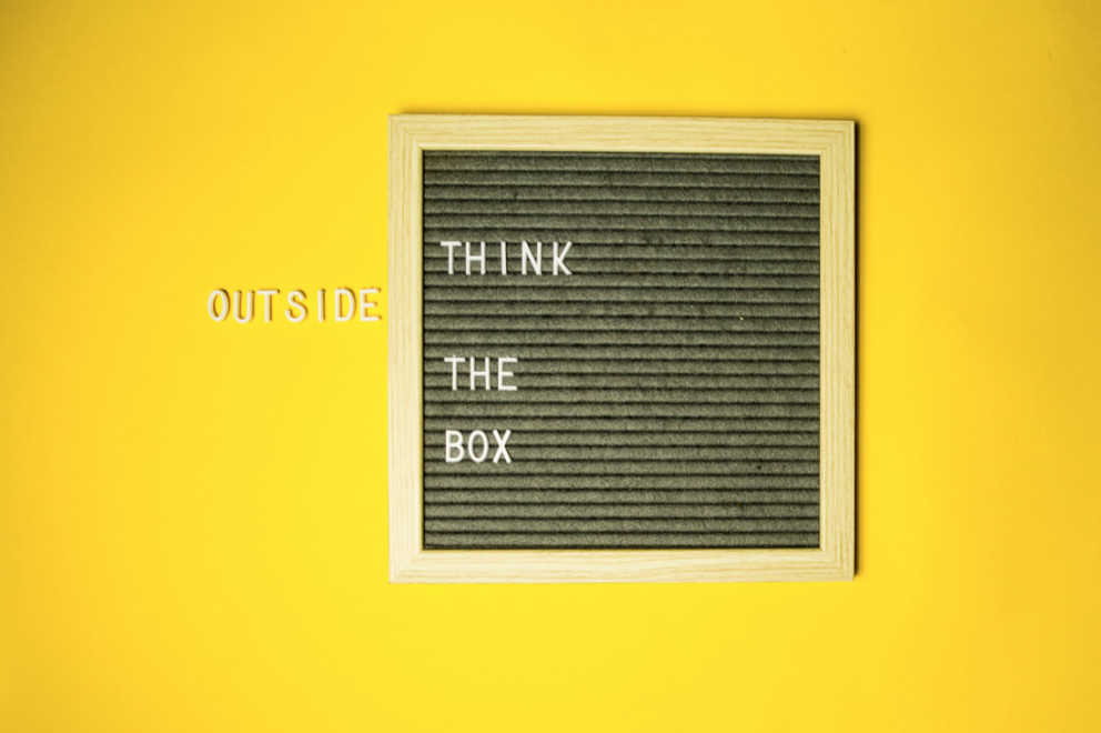 Yellow background with black box that states Think Outside The Box.