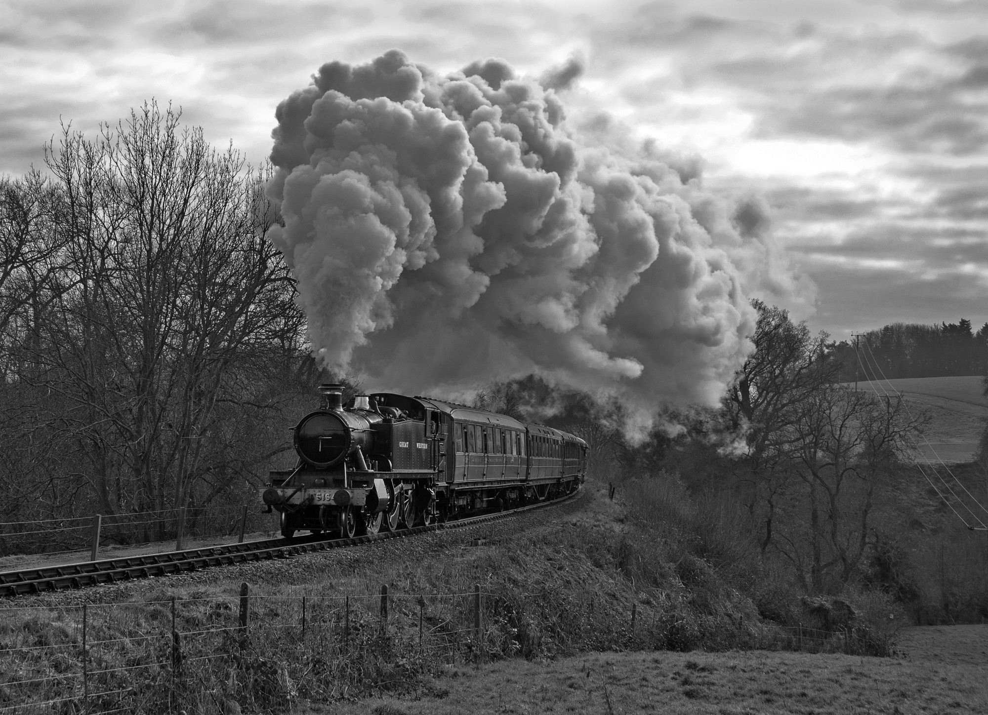 Black and white photograph of a steam engine belching smoke, thundering through the English countryside