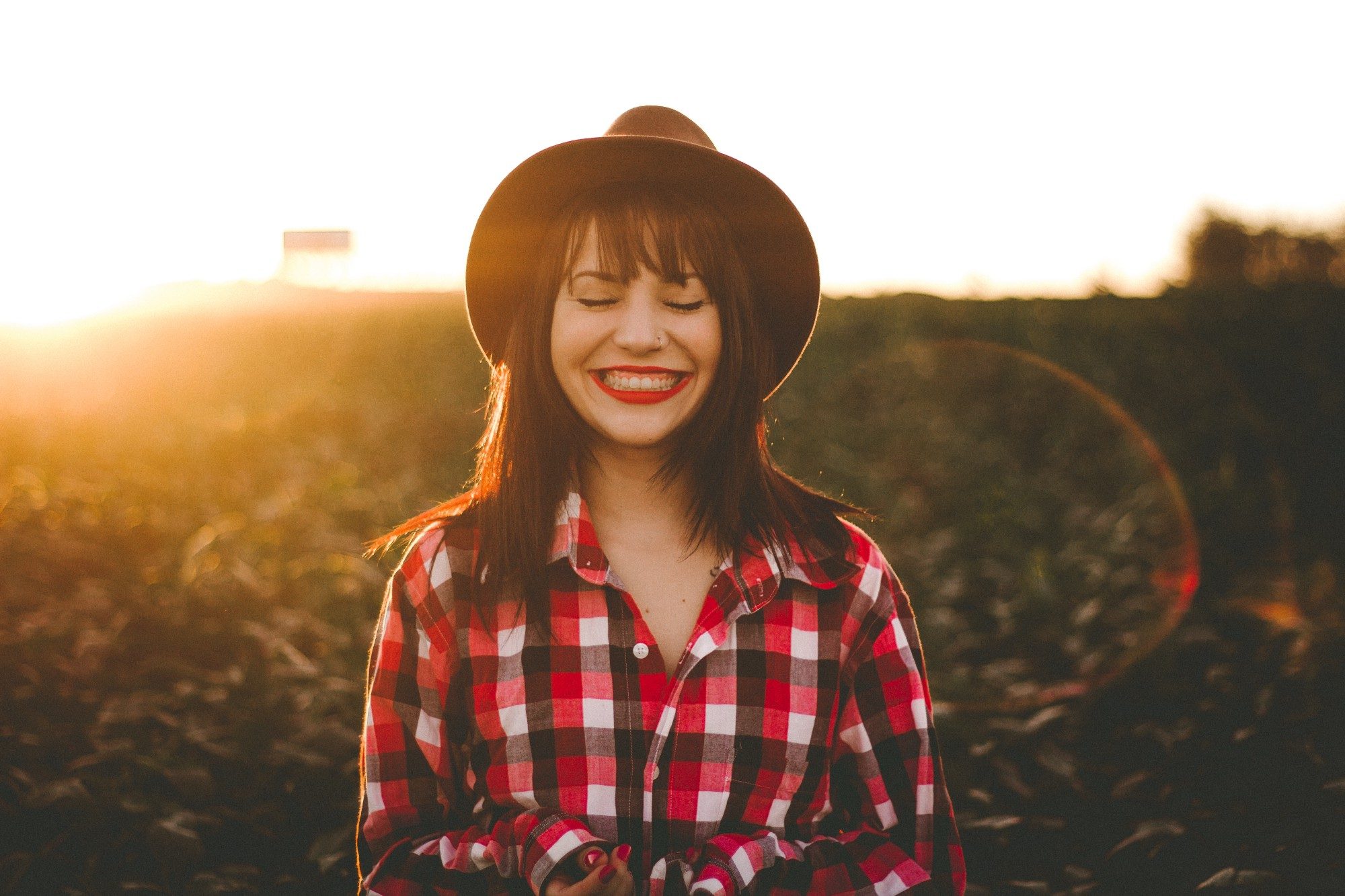 A woman standing in a field smiles broadly.