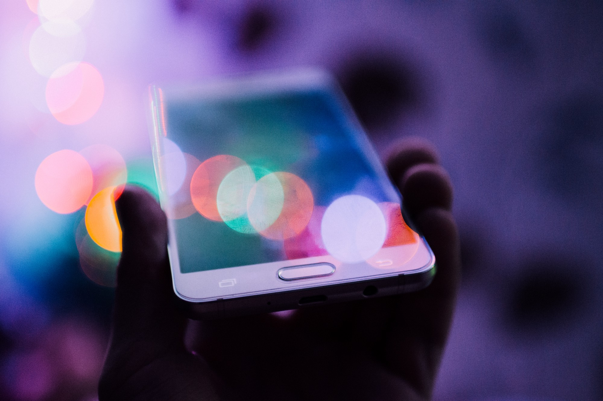 A hand holding up an iPhone in a flurry of colors