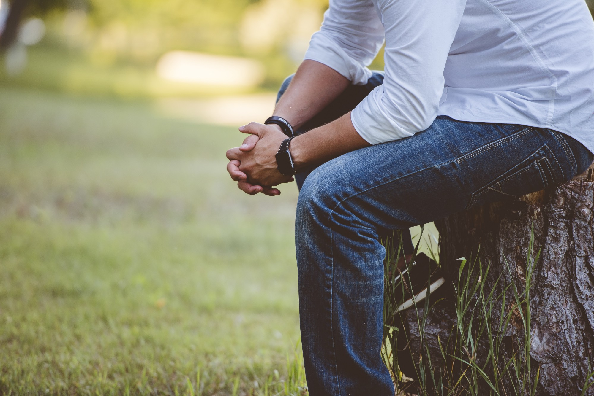 Man in blue jeans and a white shirt praying
