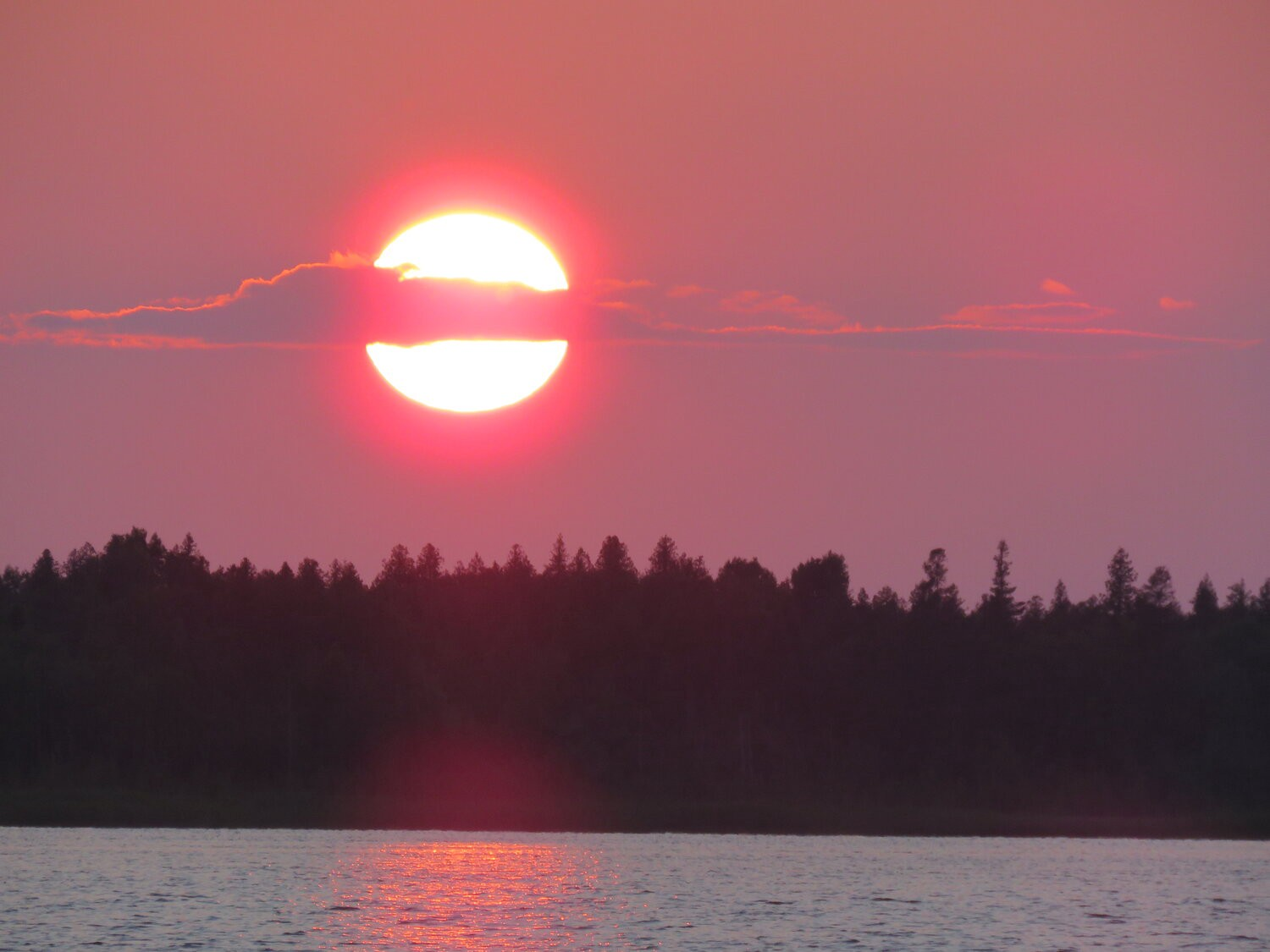 Red sunset over lake and trees