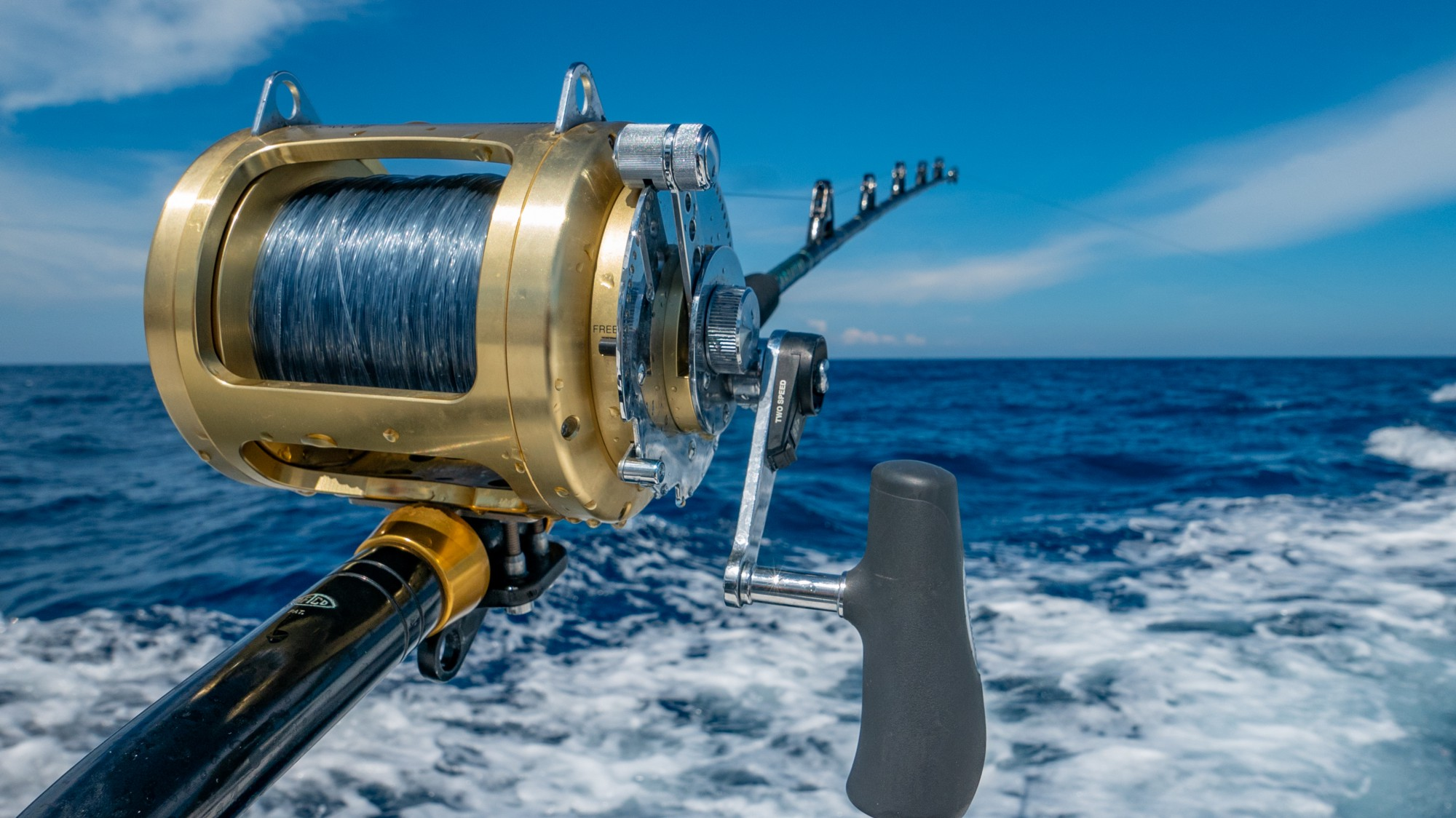 A fishing rod with a hook hanging over the back of a boat in the middle of the ocean