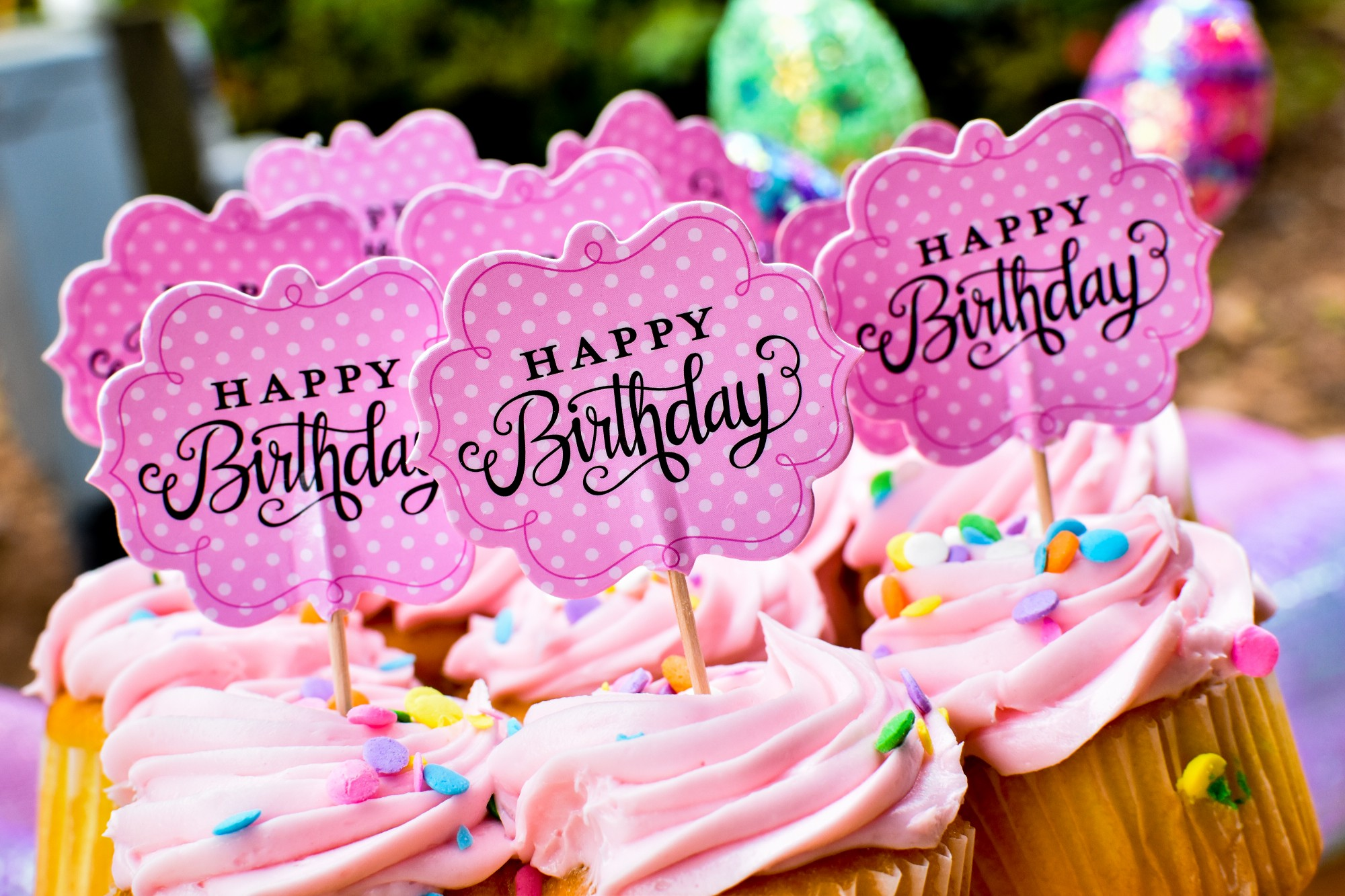 A cluster of pink cupcakes, swirled frosting, a Happy Birthday flag in each, with sprinkles to celebrate increasing your longevity