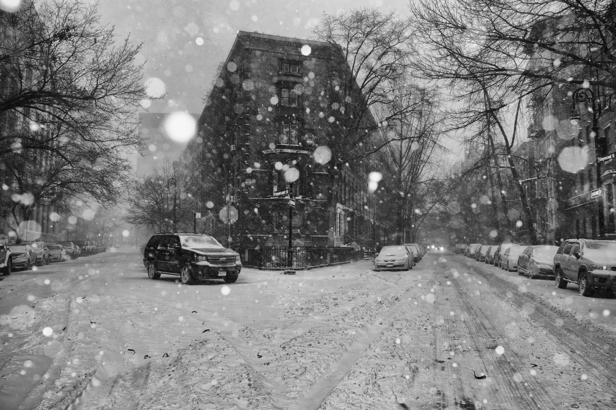 Intersection of city streets during heavy snowfall. Tall buildings and trees, cars parked, one car driving, cinders on street