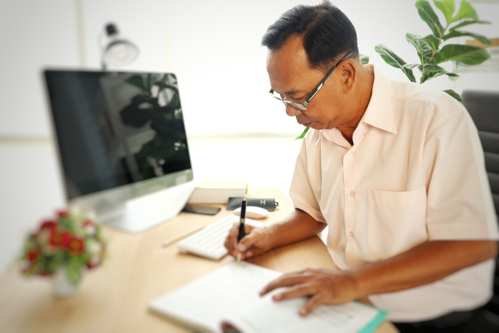 Middle-aged Asian man sitting on his office desk and signing some papers. There is a desktop on his desk and a flower vase too. Previous generations stayed at the same organization for years. This had its own advantages.