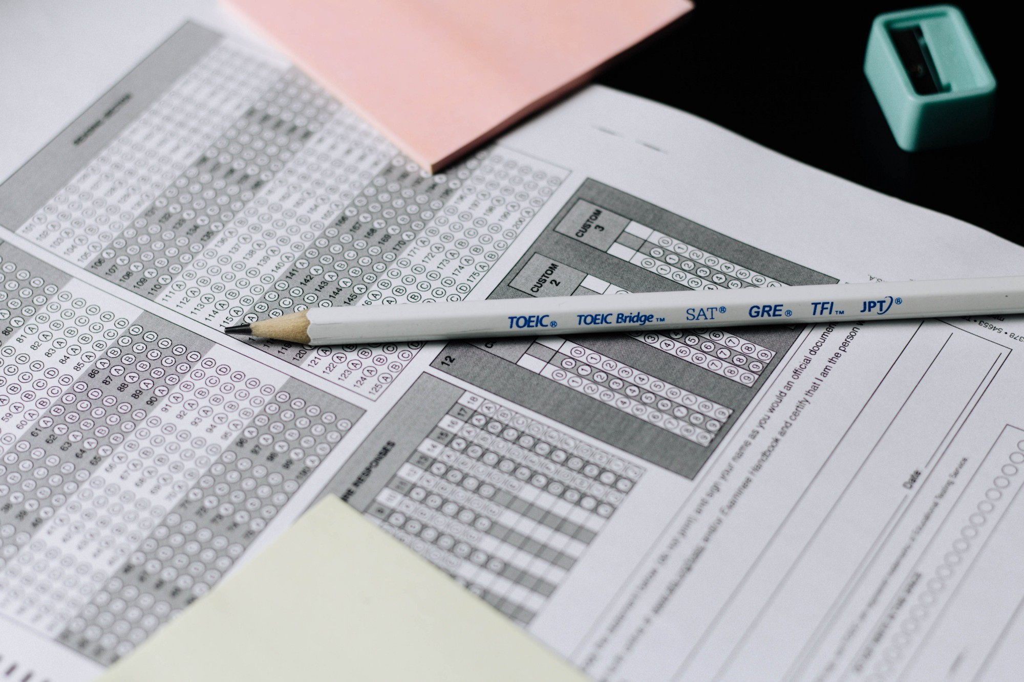 A standardized test answer sheet with a white pencil on top, post-it notepads, and a pencil sharpener nearby