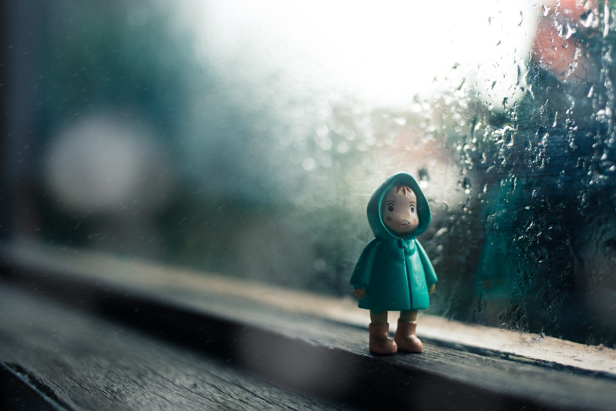 A small frowning toy in a rain jacket stands inside next to a rain soaked window. Trapped inside.