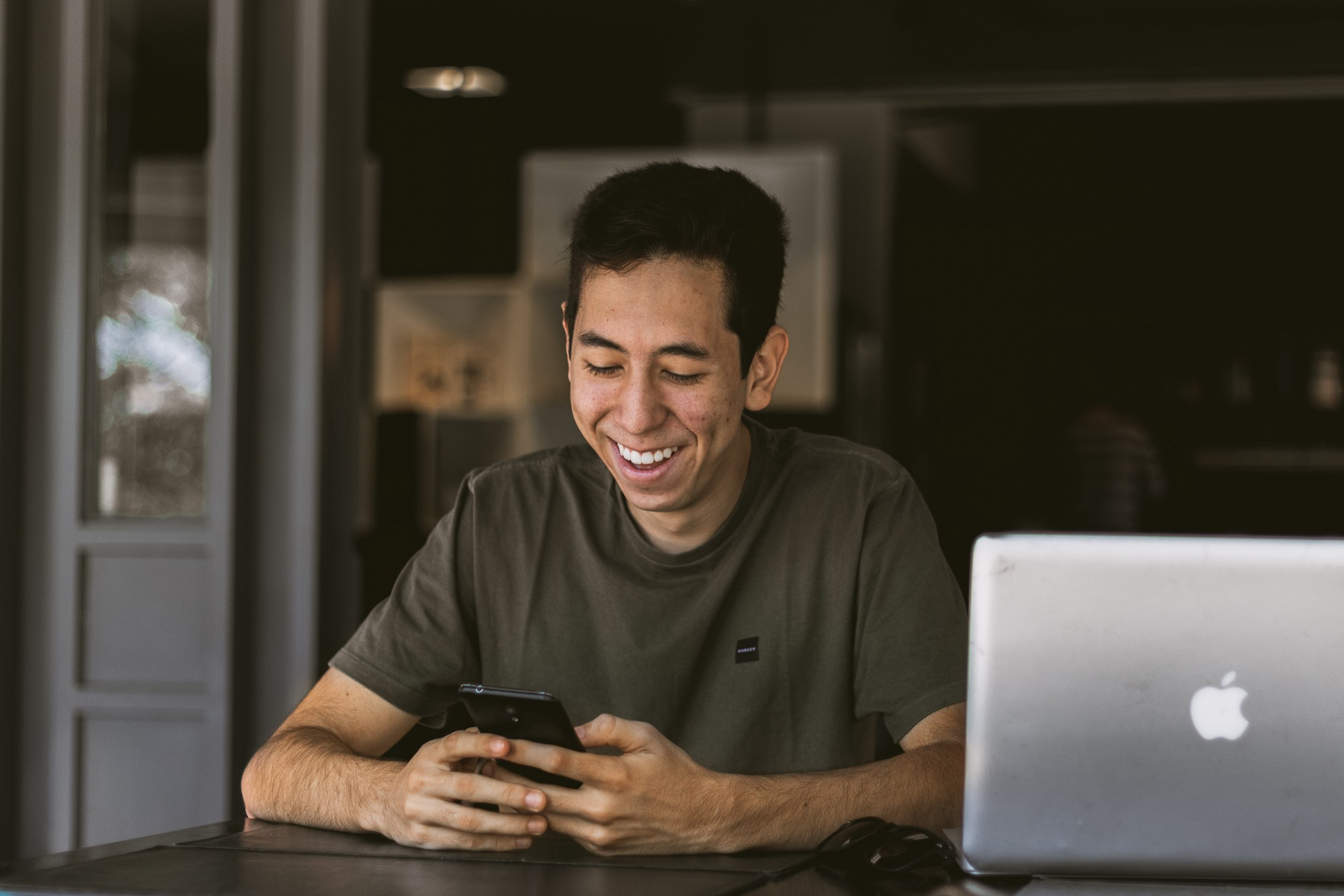 Man smiles whilst looking at his phone