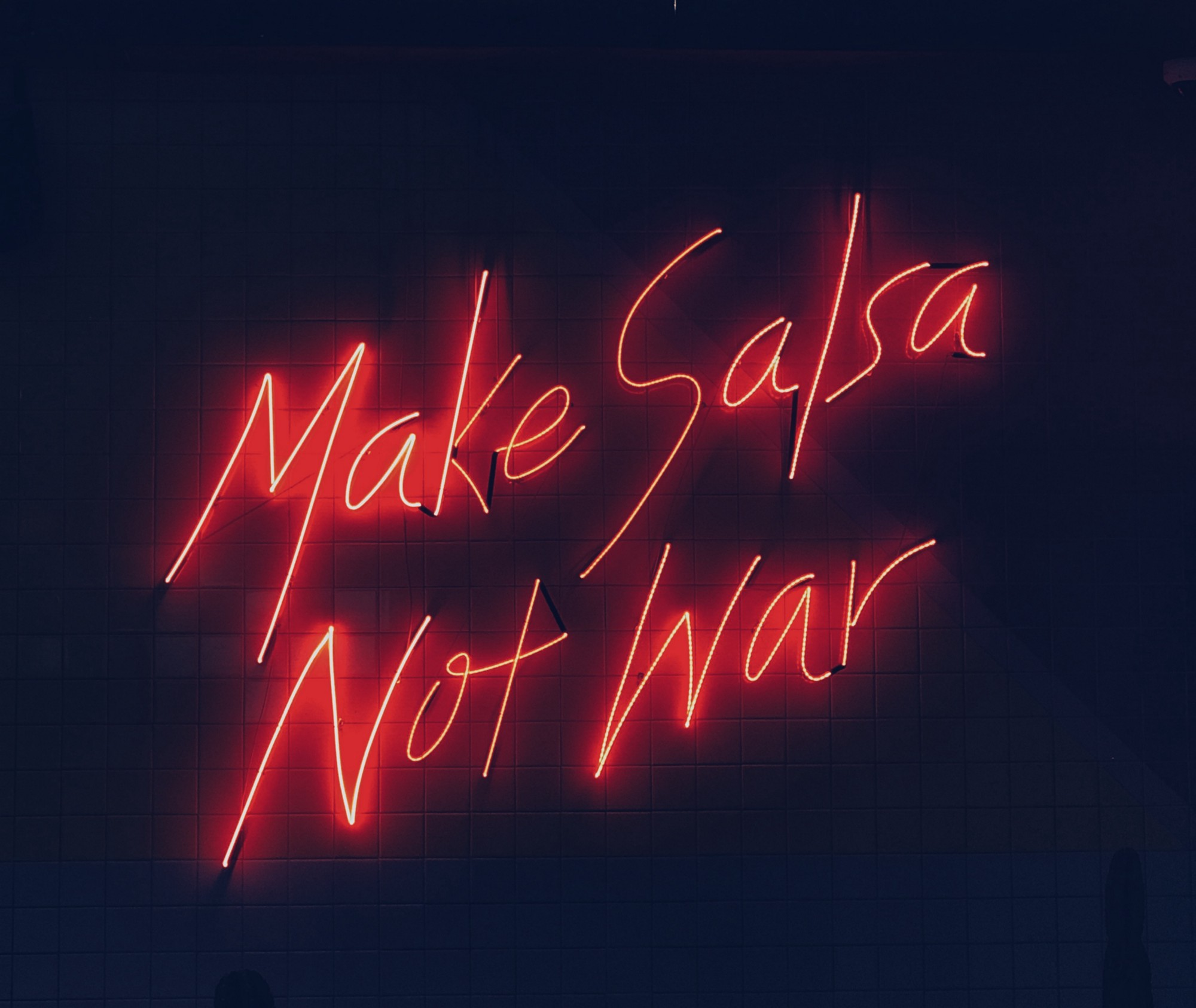 "A neon sign that reads ""Make Salsa Not War"" in red script on a dark background"