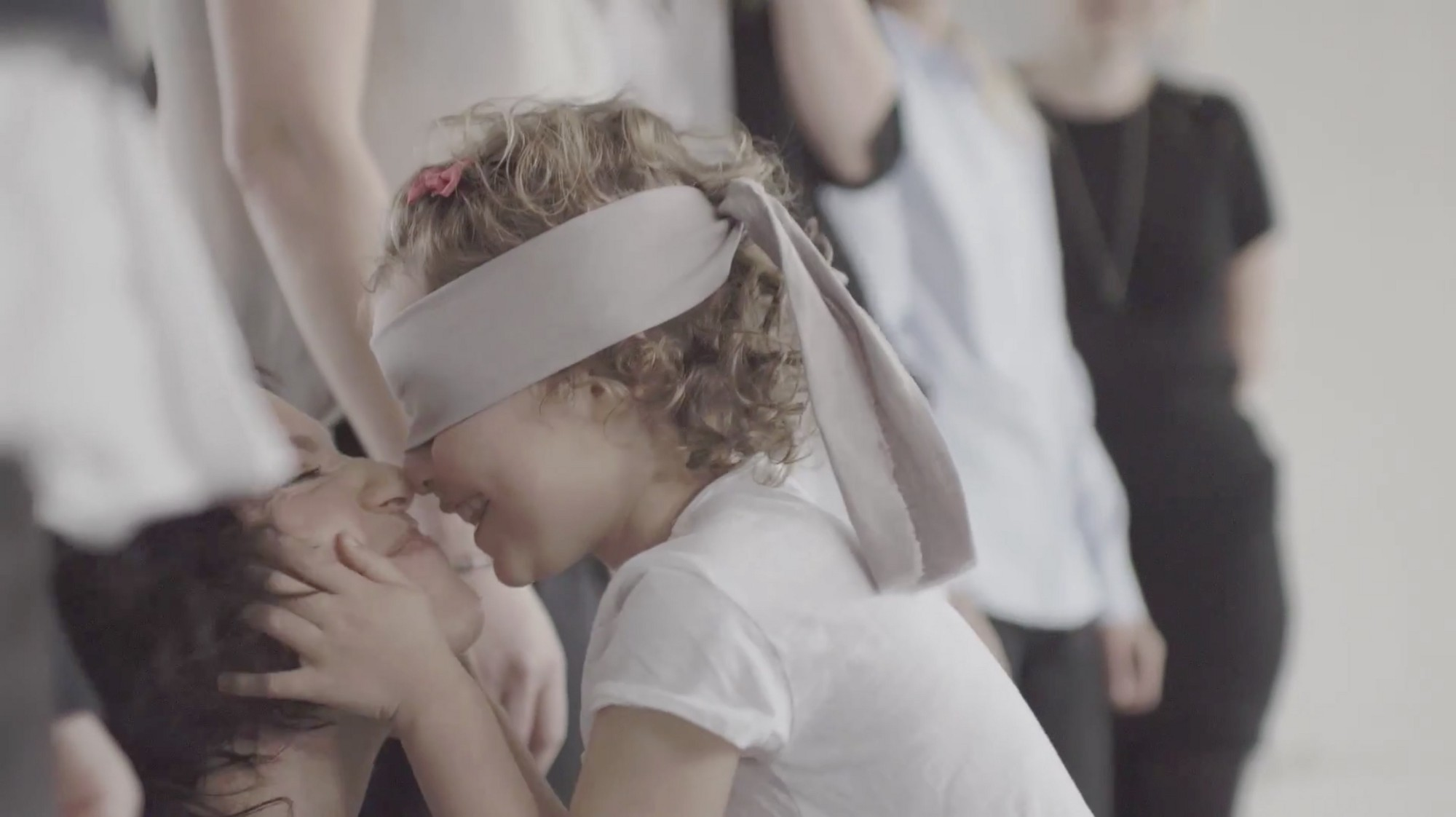 A blindfolded child and her mum laugh together.