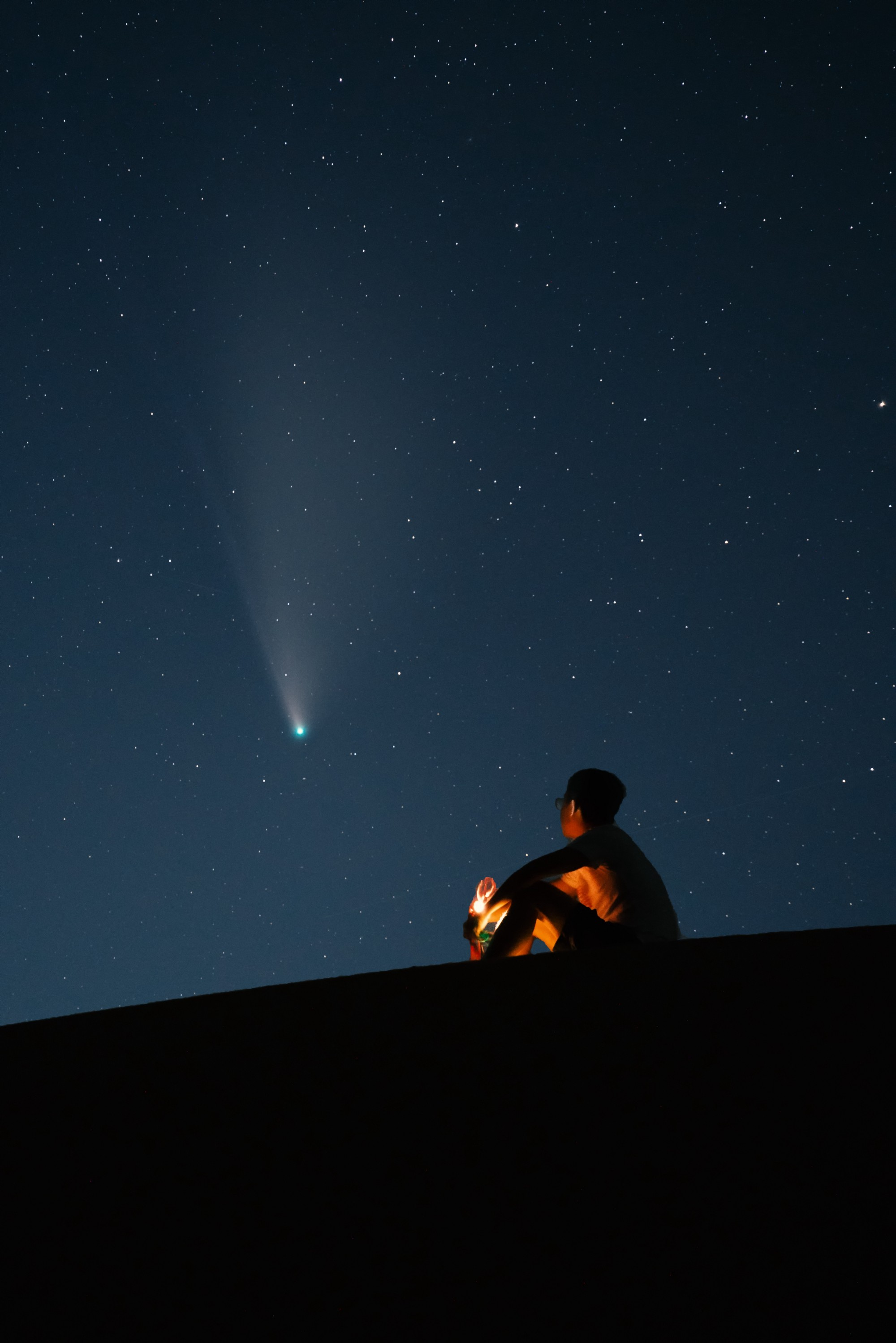 close up on nighttime image of a person sitting on earth looking up to the universe
