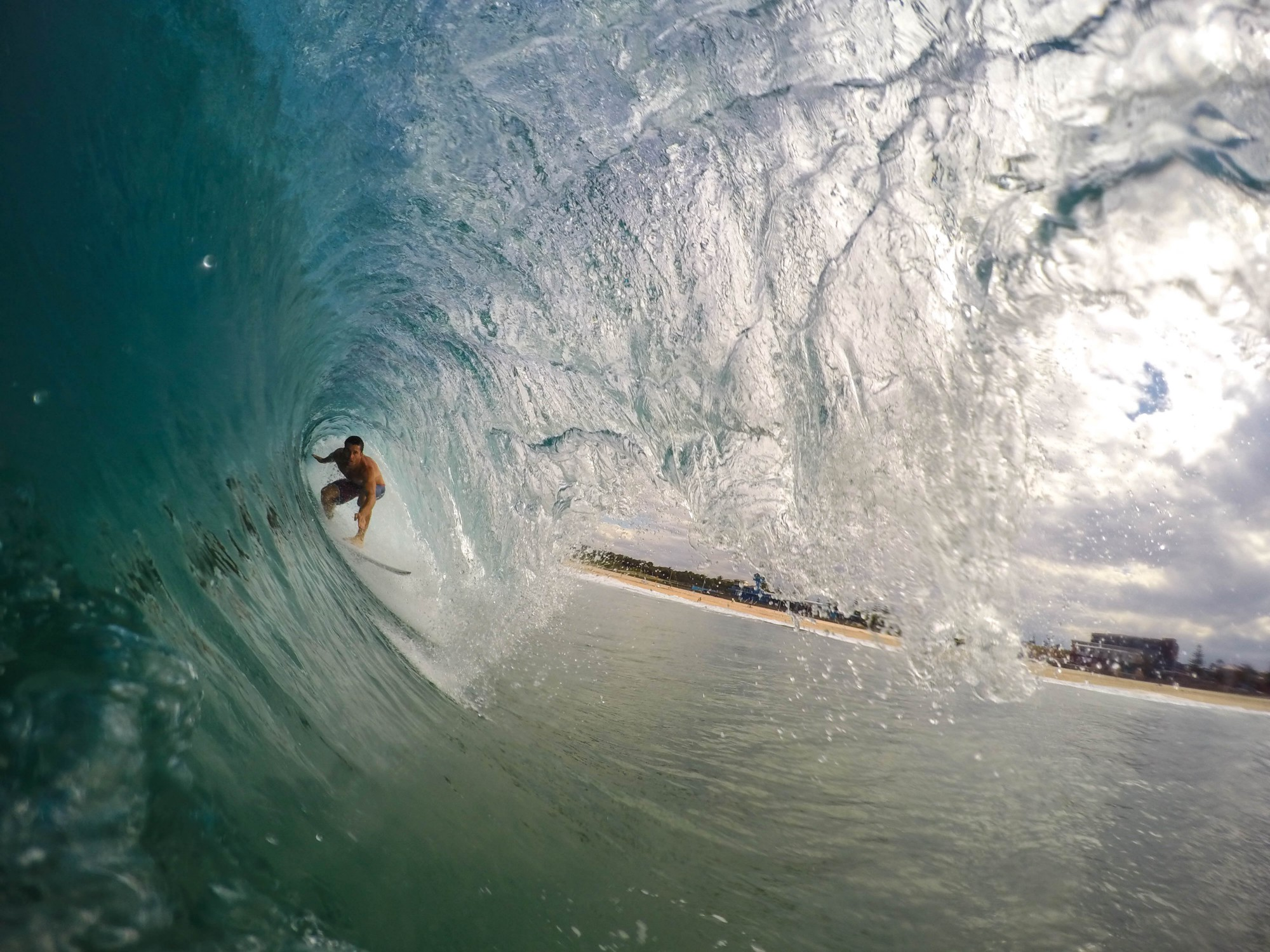 Surfer under a wave in a barrell, with water above him